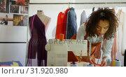 Купить «Front view of African American female fashion designer looking at cloth samples in workshop 4k», видеоролик № 31920980, снято 18 ноября 2018 г. (c) Wavebreak Media / Фотобанк Лори