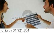 Купить «Male and female photographers checking film strips with magnifying glass 4k», видеоролик № 31921704, снято 14 июня 2018 г. (c) Wavebreak Media / Фотобанк Лори