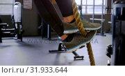 Купить «Woman exercising with rope in fitness studio 4k», видеоролик № 31933644, снято 26 июня 2018 г. (c) Wavebreak Media / Фотобанк Лори