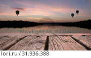 Купить «Wooden deck and hot air balloons over a lake», видеоролик № 31936388, снято 27 марта 2019 г. (c) Wavebreak Media / Фотобанк Лори