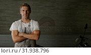 Купить «Male mechanic standing with arms crossed in motorbike repair garage 4k», видеоролик № 31938796, снято 10 февраля 2019 г. (c) Wavebreak Media / Фотобанк Лори