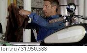 Купить «Male mechanic fixing motorbike seat in repair garage 4k», видеоролик № 31950588, снято 10 февраля 2019 г. (c) Wavebreak Media / Фотобанк Лори