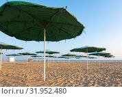 Раскрытые солнцезащитные зонты пустынного песчаного пляжа на закате солнца. Стоковое фото, фотограф Иванов Алексей / Фотобанк Лори