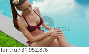 Купить «Woman in bikini applying sunscreen lotion on her body near poolside 4k», видеоролик № 31952876, снято 12 марта 2019 г. (c) Wavebreak Media / Фотобанк Лори