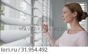 Купить «Woman looking outside through window at comfortable home 4k», видеоролик № 31954492, снято 12 марта 2019 г. (c) Wavebreak Media / Фотобанк Лори