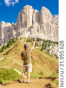 European man takes off a drone in the Alpain Dolomites in Passo Gardena. Copter pilot wants to make beautiful panoramic images and video of the mountain range Selva di Val Gardena. South Tirol, Italy. Редакционное фото, фотограф Алексей Ширманов / Фотобанк Лори