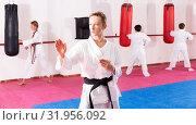 Купить «Preteen boy practicing karate movements with male trainer supervision», фото № 31956092, снято 3 июля 2020 г. (c) Яков Филимонов / Фотобанк Лори