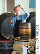 Купить «seller male middle-aged wearing apron suggesting to try glass of wine», фото № 31956508, снято 6 июня 2020 г. (c) Яков Филимонов / Фотобанк Лори