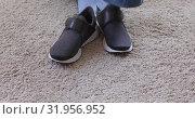 Person taking off sneakers on soft carpet. Стоковое видео, видеограф Ekaterina Demidova / Фотобанк Лори