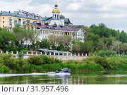 Orenburg, Russia - June, 1, 2019: Motor boat on the Ural river. City landscape with the embankment and riverbanks. Редакционное фото, фотограф Вадим Орлов / Фотобанк Лори