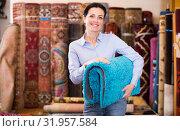 Купить «Cheerful woman customer shopping carpet in store», фото № 31957584, снято 22 ноября 2017 г. (c) Яков Филимонов / Фотобанк Лори