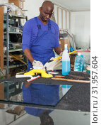 Купить «concentrated African-American workman of glass workroom standing at workplace, writing in workbook», фото № 31957604, снято 16 мая 2018 г. (c) Яков Филимонов / Фотобанк Лори