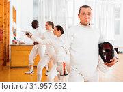Купить «Active young male fencer in uniform standing with mask and foil at fencing room», фото № 31957652, снято 11 июля 2018 г. (c) Яков Филимонов / Фотобанк Лори