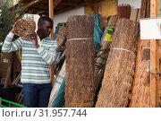 Купить «Man buying decorative fencing», фото № 31957744, снято 22 мая 2019 г. (c) Яков Филимонов / Фотобанк Лори