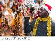 Купить «Smiling man in Santa hat selecting festive Christmas decoration», фото № 31957812, снято 8 декабря 2018 г. (c) Яков Филимонов / Фотобанк Лори
