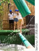 Купить «Youth in the amusement park trying to pass through an obstacle course», фото № 31958000, снято 25 августа 2019 г. (c) Яков Филимонов / Фотобанк Лори