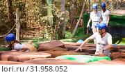 Купить «Team of friends overcomes an obstacle course in an amusement park», фото № 31958052, снято 25 августа 2019 г. (c) Яков Филимонов / Фотобанк Лори