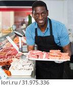 Купить «African American seller preparing fresh meat of lamb for sale in butcher store», фото № 31975336, снято 20 апреля 2018 г. (c) Яков Филимонов / Фотобанк Лори