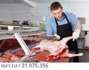 Купить «Butcher cutting lamb carcass», фото № 31975356, снято 20 апреля 2018 г. (c) Яков Филимонов / Фотобанк Лори