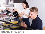 Купить «Young man working on scroll saw in architecture modeling workshop», фото № 31975416, снято 8 ноября 2018 г. (c) Яков Филимонов / Фотобанк Лори
