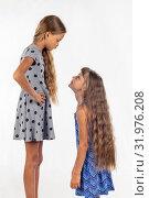 Две девочки разного роста, одна встала на стул и стала еще выше. Стоковое фото, фотограф Иванов Алексей / Фотобанк Лори