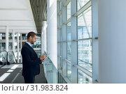 Купить «Businessman using tablet computer in office lobby», фото № 31983824, снято 21 марта 2019 г. (c) Wavebreak Media / Фотобанк Лори