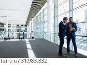 Купить «Two businessmen stand using tablet in office lobby», фото № 31983832, снято 21 марта 2019 г. (c) Wavebreak Media / Фотобанк Лори