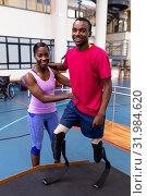 Купить «Physiotherapist helping disabled man walk with prosthetic leg on ramp in sports center», фото № 31984620, снято 24 марта 2019 г. (c) Wavebreak Media / Фотобанк Лори