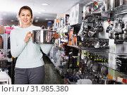 Купить «Woman is choosing saucepan for her house in the store.», фото № 31985380, снято 5 февраля 2018 г. (c) Яков Филимонов / Фотобанк Лори