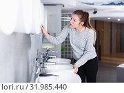 Купить «Smiling woman buyer looking ceramic washbasin with tap», фото № 31985440, снято 2 февраля 2018 г. (c) Яков Филимонов / Фотобанк Лори