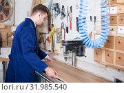 Купить «Man laying board to drill», фото № 31985540, снято 7 ноября 2016 г. (c) Яков Филимонов / Фотобанк Лори