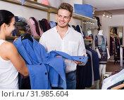 Купить «Young customers selecting jacket», фото № 31985604, снято 24 октября 2016 г. (c) Яков Филимонов / Фотобанк Лори