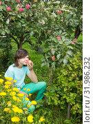 Купить «Девочка в саду вдыхает аромат яблока», фото № 31986232, снято 5 августа 2019 г. (c) Александр Романов / Фотобанк Лори