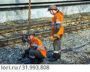 Купить «Железнодорожные рабочие подключают заземление контактного провода», фото № 31993808, снято 22 апреля 2019 г. (c) Вячеслав Палес / Фотобанк Лори