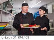 Man and woman cooks holding finished dish. Стоковое фото, фотограф Яков Филимонов / Фотобанк Лори