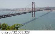 Купить «Panoramic view of 25 de Abril Bridge - suspension bridge across Tagus river connecting Lisbon city to municipality of Almada, Portugal», видеоролик № 32003328, снято 13 мая 2019 г. (c) Яков Филимонов / Фотобанк Лори