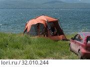 Купить «Красная беседка-палатка стоит на берегу озера возле вишнёвой машины», фото № 32010244, снято 5 июля 2019 г. (c) Светлана Попова / Фотобанк Лори