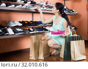 Купить «Positive woman choosing sport shoes for jogging», фото № 32010616, снято 10 мая 2017 г. (c) Яков Филимонов / Фотобанк Лори
