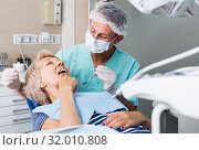Купить «male dentist with female patient during checkup in dentistry», фото № 32010808, снято 5 июля 2017 г. (c) Яков Филимонов / Фотобанк Лори