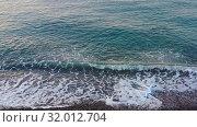 Купить «Aerial video of pebble beach natural background. Camera looks down with movement along surf line.», видеоролик № 32012704, снято 14 июля 2019 г. (c) Serg Zastavkin / Фотобанк Лори