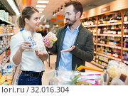 Купить «Couple is looking on shelves with variety products in the supermarket.», фото № 32016304, снято 4 апреля 2018 г. (c) Яков Филимонов / Фотобанк Лори