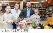 Купить «Family is standing with cart with products in the supermarket.», фото № 32016308, снято 4 апреля 2018 г. (c) Яков Филимонов / Фотобанк Лори