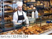 Купить «Man baker showing warm tasty croissant», фото № 32016324, снято 26 января 2017 г. (c) Яков Филимонов / Фотобанк Лори