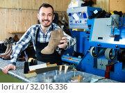 Купить «Male worker demonstrating repaired shoes in shoe», фото № 32016336, снято 2 февраля 2017 г. (c) Яков Филимонов / Фотобанк Лори
