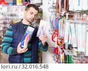 Young male customer buying new fishing wobbler in shop. Стоковое фото, фотограф Яков Филимонов / Фотобанк Лори