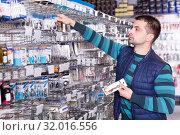 Купить «concentrated male customer choosing fishing hooks near stand in the sports shop», фото № 32016556, снято 16 января 2018 г. (c) Яков Филимонов / Фотобанк Лори