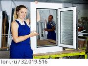 Купить «Girl in workwear with finished window», фото № 32019516, снято 19 июля 2017 г. (c) Яков Филимонов / Фотобанк Лори