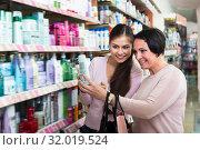 Купить «Two positive women picking cream from shelf», фото № 32019524, снято 17 августа 2019 г. (c) Яков Филимонов / Фотобанк Лори