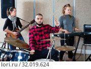 Купить «Expressive drummer with his bandmates practicing in rehearsal room», фото № 32019624, снято 26 октября 2018 г. (c) Яков Филимонов / Фотобанк Лори