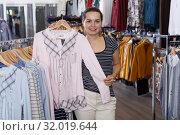 Купить «Woman demonstrating blouse on hanger», фото № 32019644, снято 10 октября 2018 г. (c) Яков Филимонов / Фотобанк Лори